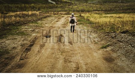 A Woman Is Walking On A Country Road Through Yellow Fields. Female Photographer. Vintage Effects. Wa