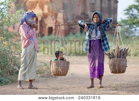 Woman Carrying Baby And Firewood In Basket Over Fields In Bagan, Mandalay Division, Myanmar