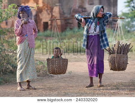 Burmese Women  In National Clothes With Baby And Firewoods Walking On The Road To Old Bagan, Myanmar