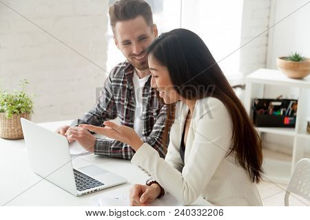 Positive Asian And Caucasian Colleagues Laughing At Funny Joke Talking At Workplace With Laptop, Div
