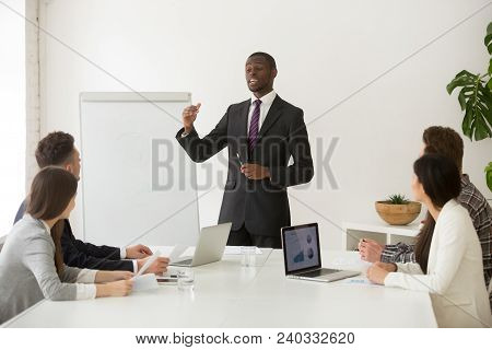 Confident African Speaker Business Coach In Suit Giving Presentation Training Sales Team In Office,
