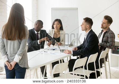 Angry African Boss Pointing On Wristwatch Reprimanding Employee Coming Too Late At Diverse Team Meet