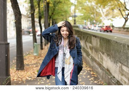 Asian Pretty Female Tourist Walking On Autumn Street With Fallen Leaves In Europe. Concept Of Intern