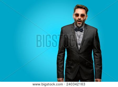 Middle age man, with beard and bow tie scared in shock, expressing panic and fear