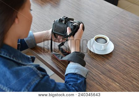 A Girl Photographer In Urban Dress Looks At Photos On Her Camera. Lunch Break In The Cafe. Hobi. Art