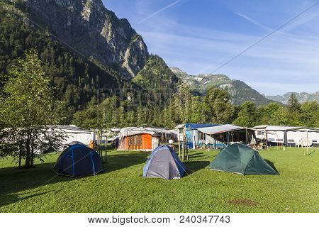 Camping In The  Alpine Mountains . Tourist Tents And Lodges In The Background Of Mountains. Summer I