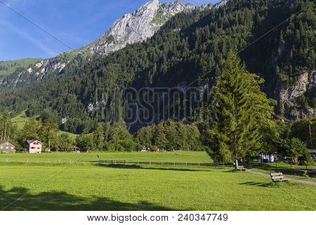 Alpine Mountain Landscape -  Green Meadow Against The Mountain And Blue Sky . Alpine Village. Swiss
