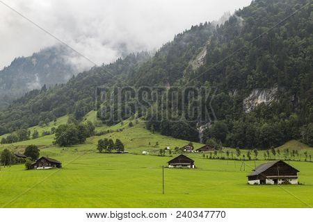Alpine Mountain Landscape -  Green Meadow Against The Foggy Mountain . Alpine Village. Swiss Alps At