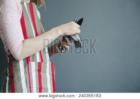 Woman Stands In Striped Apron With Small Metal Shovel And Gloves On Gray Wall Background With Copy S