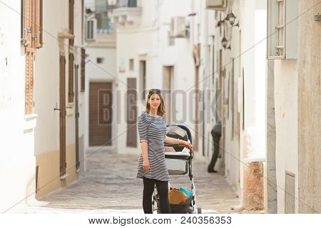 Gallipoli, Apulia, Italy - A Woman With A Stroller In A Middle Aged Alleyway