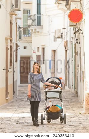 Gallipoli, Apulia, Italy - A Woman Out For A Walk With Her Baby In The Streets Of Gallipoli