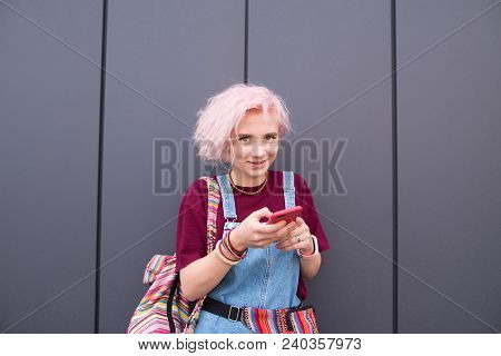 Stylish Happy Girl With Colored Hair Is With A Smartphone On A Dark Background. Smiling Girl Hipster
