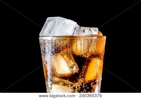 Stream Of Soda Being Pouring Into A Glass With Soda And Ice Cube On Black Background, Closeup Textur