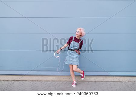 Portrait Of A Fashionable Girl In Stylish Clothes, Pink Hair And Sunglasses Poses Against The Backdr