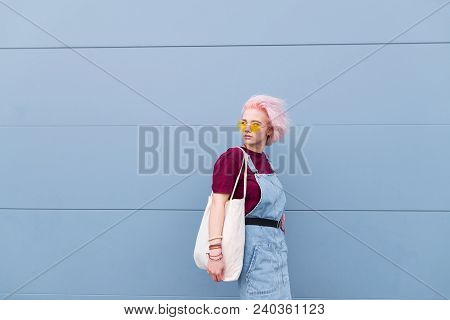 Cute Girl With A Shopper In Her Hands Against The Background Of A Blue Wall. Portrait Of A Stylish C