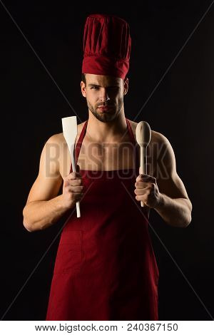 Kitchen Utensils Concept - Serious Bearded Man In Cook Hat And Apron With Wooden Kitchen Spatula And