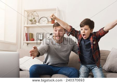 Father and son watching football on TV at home. Emotional man and little boy cheering their favorite team, family enthusiasm, copy space poster