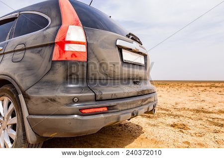 Back View Of A Very Dirty Car. Fragment Of A Dirty Suv. Dirty Rear Lights, Wheel And Bumper Of The O