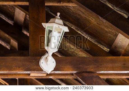 A Small White Lantern On The Beam Under The Slope Of Roof Closeup