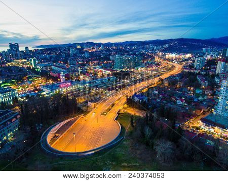 Beautiful Drone View Of City, Mountains And Doubler Of Kurortnyy Prospekt Highway At Twilight, Sochi