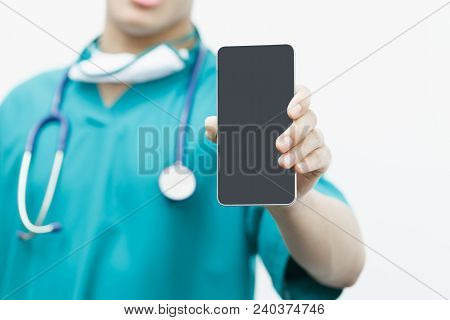 Asian Smart Doctor Holding Smartphone Computer With Hand. Surgeon Has Stethoscopes. Concept Of Medic