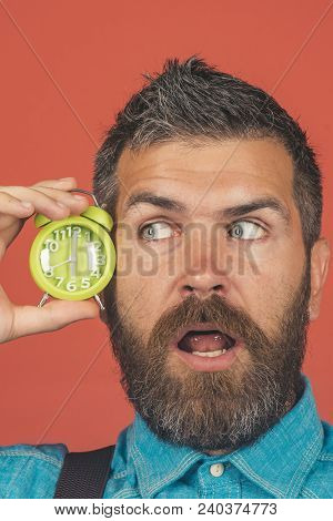 Surprised Excited Bearded Man Hold Alarm Clock Near Face. Bearded Man With Alarm Clock On Red Backgr