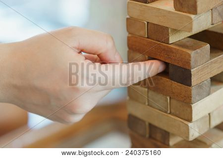 Hand Of Woman Playing A Block Wood Game. Tower Stack From Wooden Blocks Toy.