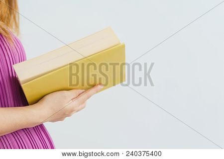 Close-up Of Beautiful Pregnant Woman Reading Yellow Book And Her Handsome Husband Hugging The Tummy.