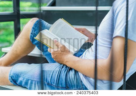Portrait Handsome Man Sitting At Stairs University Library, Reading Book And Relaxing. Hipster Weari