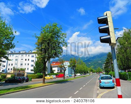 Fulpmes, Austria - May 31 2017: Traffic Signal And Parked Cars On Empty Road On A Clear Day.