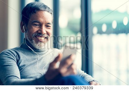Portrait Smiling Attractive Mature Man Retired With White Stylish Short Beard Using Smartphone Or Li