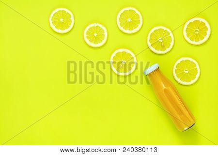 Beautiful Food Art Background. Yellow Juice In Glass Bottles Sliced Lemon Fruit On Bright Green Surf