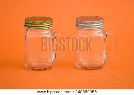 Empty Salt, Pepper Shakers On Orange Background