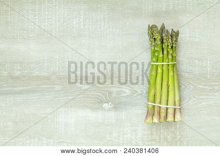 Beautiful Food Art Background. Asparagus Sprouts On Light Wooden Surface.