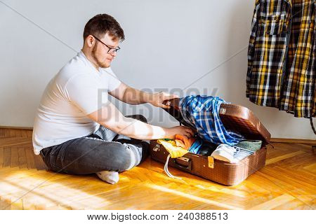 Man Can't Fit All Staff In Suitcase. Travel Concept. Man Need Help To Gather Clothes. Copy Space