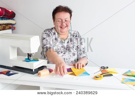 Work, Manufacturing, Quilting Concept. There Is An Old And Professional Seamstress At Her Work Table
