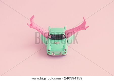 Miniature Retro Car With Doll Boots On Pastel Pink Background. Sex In The Car On First Date Minimal