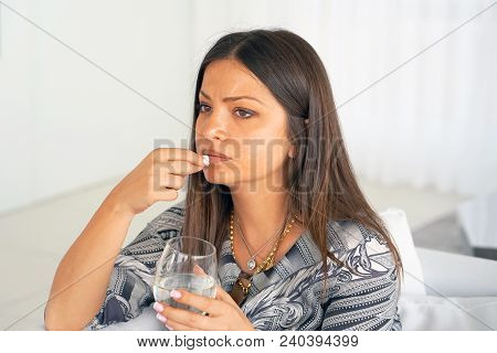 Sick Woman Holding Pill Glass Of Water At Home On The Sofa. Depressed Unhealthy Woman, About To Take