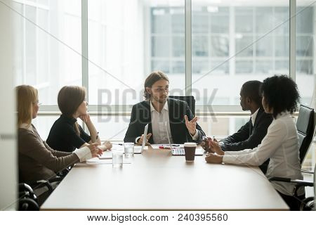 Serious Ceo Leading Corporate Team Meeting Talking To Multi-ethnic Employees Giving Instructions, Co