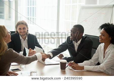 African Businessman And Caucasian Businesswoman Shaking Hands Over Conference Table At Multiracial M