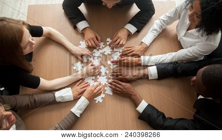 Diverse Team People Assembling Jigsaw Puzzle, Multiracial Group Of Black And White Colleagues Engagi