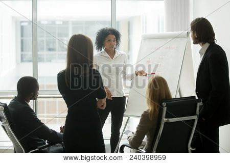 Serious African Female Leader Or Coach Gives Presentation Of New Marketing Plan At Sales Team Meetin