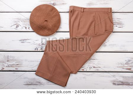 Classic Brown Trousers For Women. Female Beige Beret And Trousers On White Wooden Background. Collec