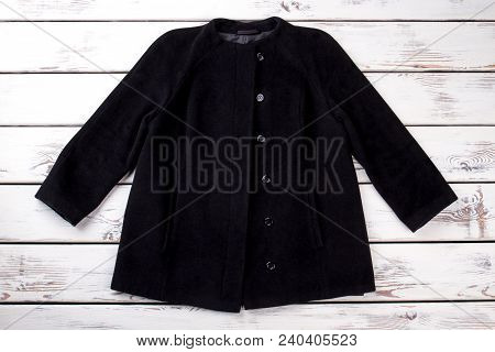 Female Short Black Coat. New Woman Autumn Coat On White Wooden Background. Female Fall Outfit.