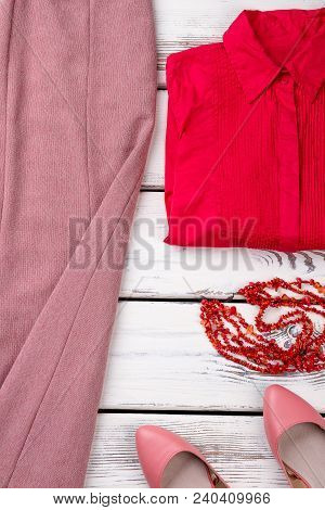 Elegant Female Apparel On Wooden Table. Ladies Red Blouse, Necklace And Sandals. Women Fashion Garme