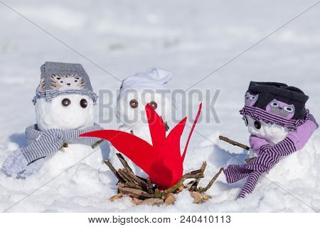 Cute Little Snowmen Dressed For Winter, Huddled Around A Camp Fire Trying To Keep Warm. Snow Covered