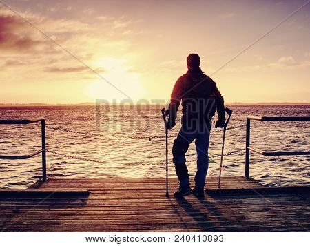Hurt Man With Hooded Jacket And Forearm Crutches  Looking Sadly Into Sea Water. Traveler  Stand On S