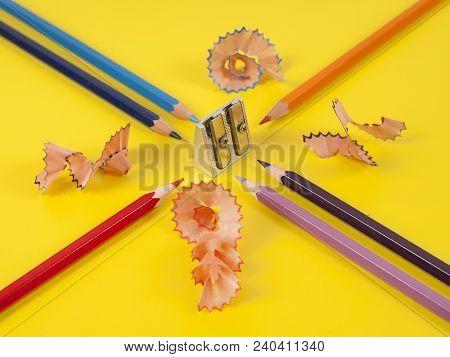 Some Colored Pencils Of Different Colors And A Pencil Sharpener And Pencil Shavings On а Yellow Back