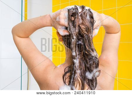 Attractive Woman Washing Her Hair With Shampoo In Shower