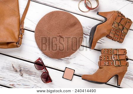 Stylized Set Of Female Fashion Outfit. Stylish Women Brown Boots And Accessories On White Wooden Bac